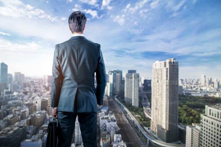 businessman looking down a modern city. business prospect concep