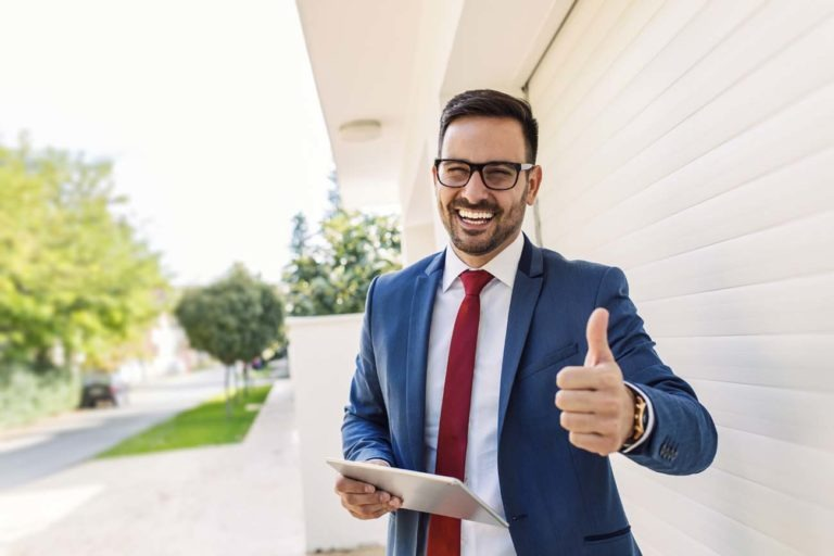 Handsome young smiling salesman giving thumbs up